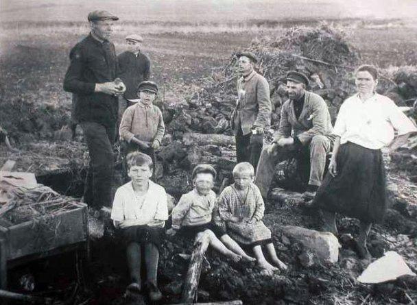 Група з п'яти дорослих і чотирьох дітей з тачкою в оточенні старих будматеріалів
