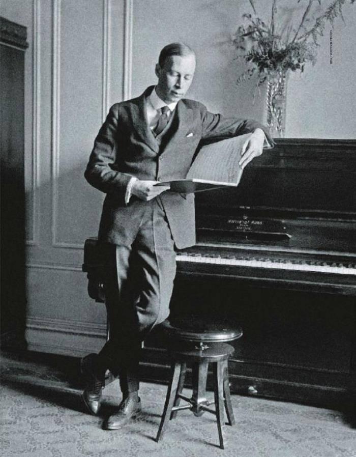 Молодий Сергій Прокоф'єв читає ноти спершись на рояль