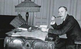 Сергій Прокоф'єв сдить за столом, тримаючи в зубах трубку.